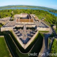 View of Fort Ticonderoga shaped like an arrowhead, plush green trees and water surrounding fort.