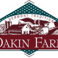 Diamond shaped teal sign with white dots, sketch of farm scene with barn and house Banner Dakin Farm established 1792.
