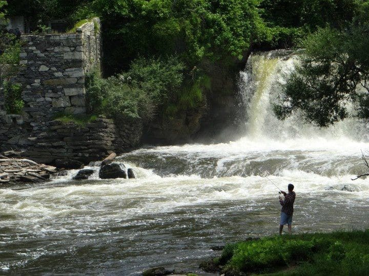 Man with blue shorts and t-shire fishing in the lake surrounded by plush green trees and waterfall in the background.