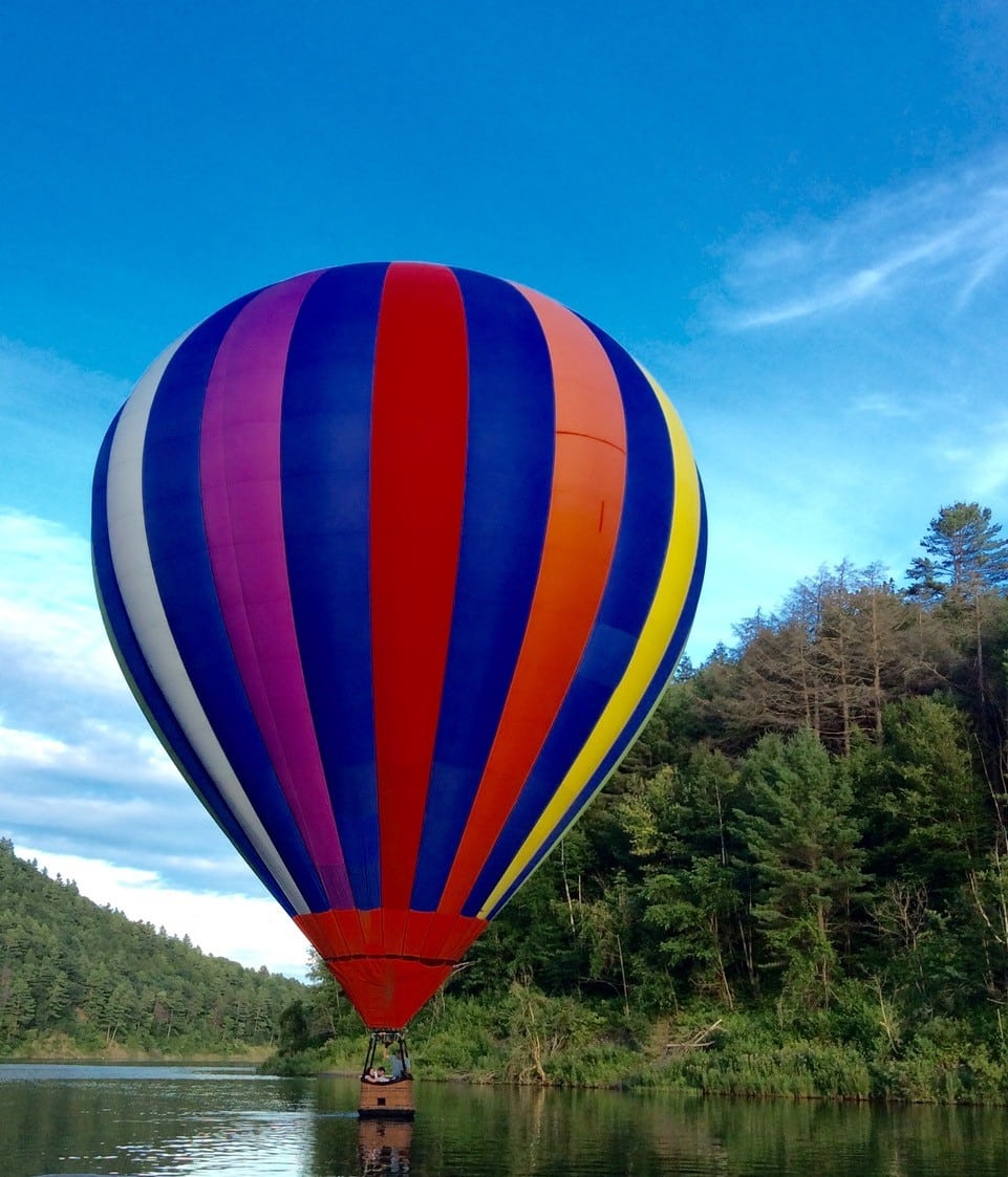 Multi-color Striped hot air balloon sitting on lake surrounded by trees and bushes with blue sky and white clouds in background.