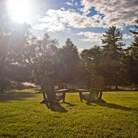 two adirondack chairs basking in the sunlight on the Swift House inn lawn