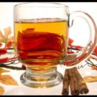 Large clear mug with apple cider, cinnamon sticks with Fall leaves laying on table