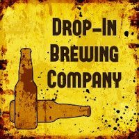 Two beer bottles on Yellow and tan sign with black lettering Drop-In Brewing Company