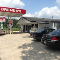 White building with red and white sign Brenda's Country Store, ice machine in front and cars in lot