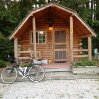 Small log cabin with bike sitting out front on gravel with trees surrounding. Flowers in planter and wooden picnic table