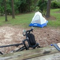 Camping area with blue and white tent, bike leaning against wooden picnic table with tall trees surrounding.