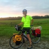 Biker with helmet, black short and yellow shirt standing over bike with packs next to green fields with trees behind.