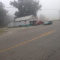 White building in the distance through foggy, rainy conditions. Red and blue car in distance by store, 2 Lane road