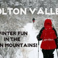 Person using hiking poles wearing red and black coat walking on snow-covered trail. Bolton Valley! Winter Fun