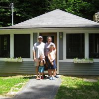 Family standing on concrete sidewalk in front of small grey building with chimney and hanging flower planters.