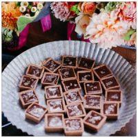 Platter of chocolates next to flowers, photo by sasha zvereva on www.unsplash.com