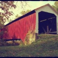 Red and white painted covered bridge elevated with garage-like opening , surrounded by trees during fall
