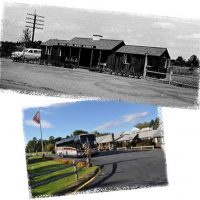 Original store with antique white car to store in at present time with Greyhouse Bus, American flag on pole