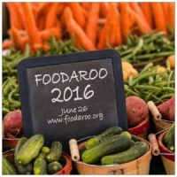 Baskets with handles filled with vegetables (carrots, green beans, zucchini). Black sign with white lettering Foodaroo 2016.