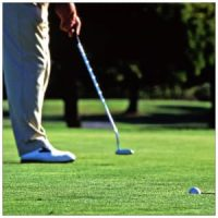 Person with long pants and white shoes making a putt on a golf course
