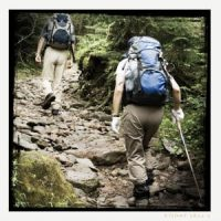 Two people hiking with packs on their backs on rocky terrain