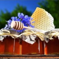 Metal container with Honeycomb, honey dipper and purple flowers, tall plush treen and clear blue sky in background