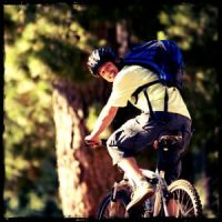 Man with backpack on bicycle in the woods