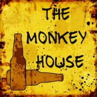 Two beer bottles on Yellow and tan sign with black lettering The Monkey House