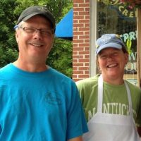 Man with blue t-shirt and woman with green t-shirt and white apron standing in front of red brick Otter Creek Bakery.