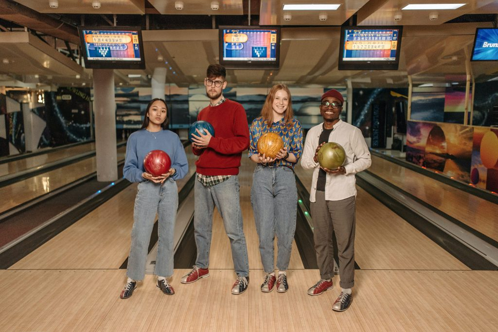 4 young people holding a bowling ball in their hands.