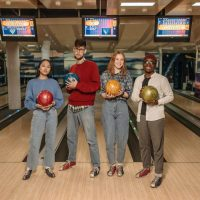 4 young people with bowling balls in their hands.
