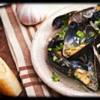 White Plate on maroon and white striped placemat with Mussels, French bread sittng on table