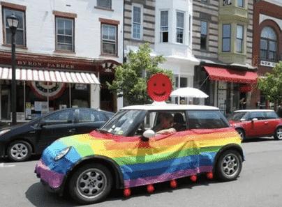 A small car in LGBTQ colors in a caravan.