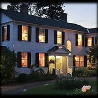 Side-view of white house with black shutters at night with lights shining through the vast windows, porch lit, bushes.