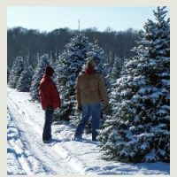 Man in brown coat and women in red coat and hat standing in snow surrounded by snow covered evergreen trees.