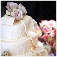 3-Tier white wedding cake with white streamers, ivory flowers on top, bouquet of pink flowers in background.