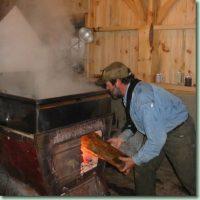 Man wearing blue denim shirt, brown pants and brown ballcap putting log into wood-burning smoking stove, Wood walls.