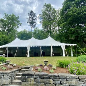 white tent on green lawn with stone wall
