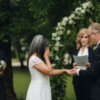 wedding under arbor with officiant and bridesmaid